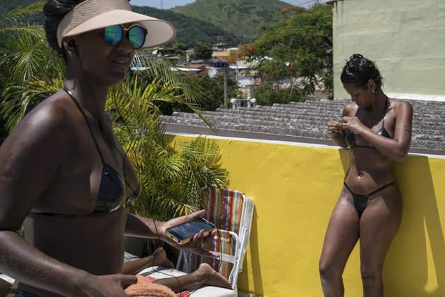In this January 11, 2017 photo, women in search of crisp tan lines wear bikinis made of black electrical tape at the Erika Bronze rooftop salon in the suburb of Realengo in Rio de Janeiro, Brazil. Tanners who don't want sunblock or want to stay out longer than recommended must sign a disclaimer absolving the salon of liability. (Photo by Renata Brito/AP Photo)