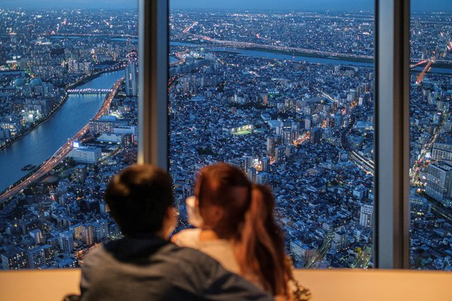 A couple watches office and residential buildings from the observation deck of Tokyo Skytree, the world's tallest broadcasting tower, in Tokyo, Japan, August 18, 2021. (Photo by Marko Djurica/Reuters)