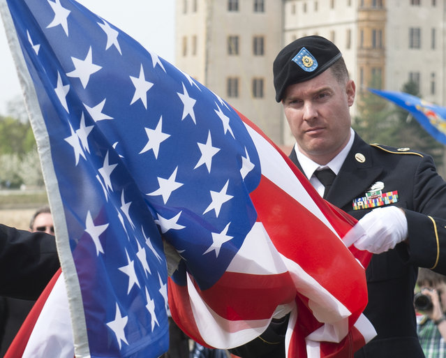 A US soldier hoists the US flag during the 70th anniversary celebrations of the Elbe Day in Torgau, eastern Germany, Saturday, April 25, 2015. The WW II link-up of US and Soviet Forces occurred here at the river Elbe on April 25, 1945. (AP Photo/Jens Meyer)