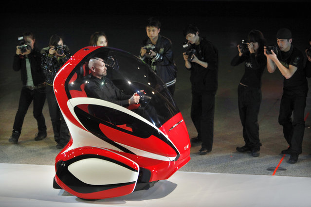 """An EN-V, or """"Electric Networked-Vehicle"""", is driven by a General Motors' staff member during an event to unveil its concept car in Shanghai, March 24, 2010. (Photo by Nir Elias/Reuters)"""