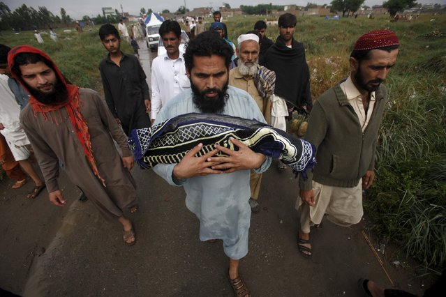 A man carries the body of his son for burial after he was killed when a rooftop of his house collapsed due to heavy rain in the outskirts of Peshawar, Pakistan April 27, 2015. (Photo by Fayaz Aziz/Reuters)