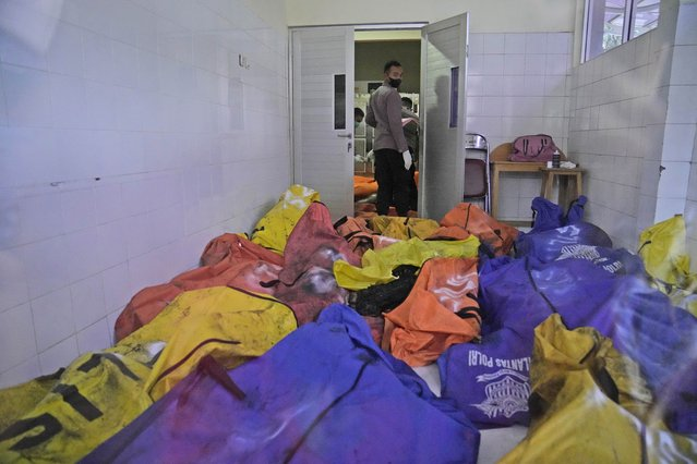 A police officer stands near body bags containing the bodies of the victims of a prison fire at the local hospital's morgue in Tangerang on the outskirts of Jakarta, Indonesia, Wednesday, September 8, 2021. (Photo by Dita Alangkara/AP Photo)