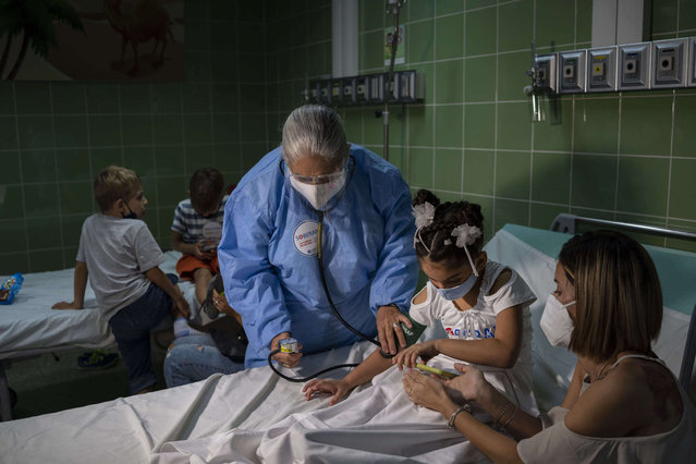A nurse takes a girl's blood pressure after giving her a dose of the Cuban-made Soberana-02 vaccine for COVID-19 in Havana, Cuba, Tuesday, August 24, 2021. (Photo by Ramon Espinosa/AP Photo)