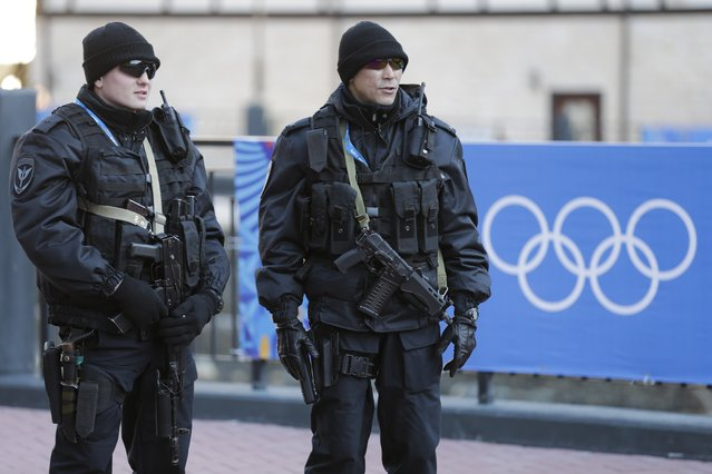 Russian security forces stand guard as the Olympic torch makes it's way through the streets of the Rosa Khutor ski resort in Krasnaya Polyana, Russia at the Sochi 2014 Winter Olympics, Wednesday, February 5, 2014. (Photo by Gero Breloer/AP Photo)