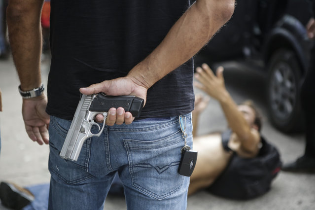 A Civil Police officer stands guard over a looter shot in the leg by the Civil Police while looting an electronic store in Vitoria, Espirito Santo state, Brazil, Monday, February 6, 2017. Protests by the friends and family of military police in Espirito Santo have led to an increase in crime and forced the shut-down of some state services, authorities said Monday. (Photo by Diego Herculano/AP Photo)