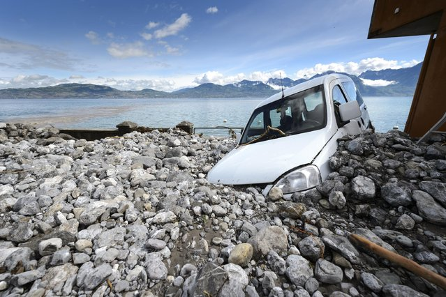 A car is stucked in  stones and mud in St. Gingolph, Switzerland, May 2, 2015. The river La Morge, which is the border between Switzerland and France, is out of bed after heavy rainfalls. Several houses with two restaurants, a hotel and two cars were heavily damaged and flooded. (Photo by Laurent Gillieron/Keystone via AP Photo)