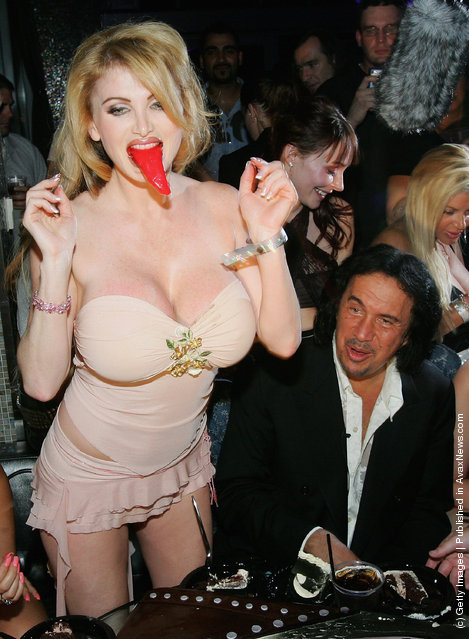 Kiss singer/bassist Gene Simmons watches as adult film actresses Sara Jay (L) and Taylor Wane play with the tongue from his birthday cake during his birthday party at the Palms Casino