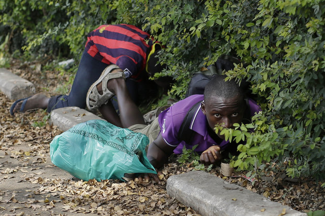 Men duck for cover as shots are fired in Bujumbura, Burundi, Monday, May 4, 2015. (Photo by Jerome Delay/AP Photo)