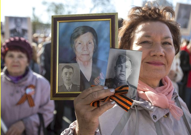 A woman holds portraits of World War Two participants during the Immortal Regiment march as part of the Victory Day celebrations in Blagoveschensk, Russia, May 9, 2015. (Photo by Reuters/Host Photo Agency/RIA Novosti)
