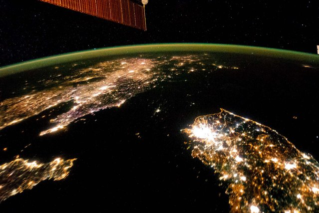 This January 30, 2014 photo made available by NASA on February 25, 2014, shows North Korea, darker area at center, between South Korea, right, and China, left. Lights from the North Korean capital, Pyongyang, are visible at center. The image comparing the night time lights of the countries was made by the Expedition 38 crew aboard the International Space Station. (Photo by NASA)