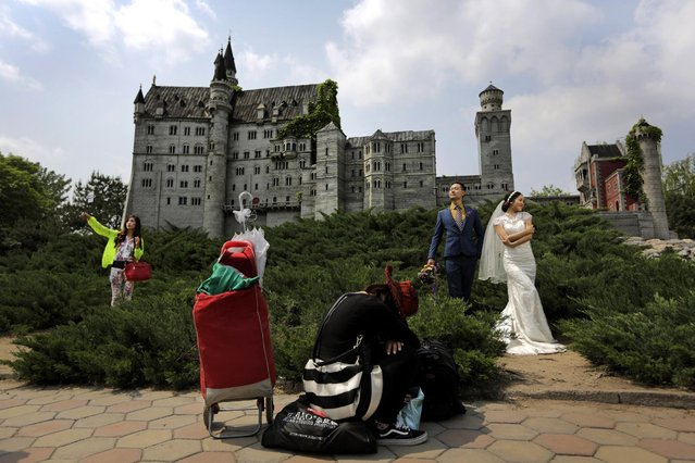 A woman uses a selfie stick to take souvenir photo of herself next to a bride and groom posing for wedding photos against a replica Germany's Neuschwanstein Castle at the World Park in Beijing, China, Saturday, May 2, 2015. (Photo by Andy Wong/AP Photo)