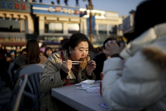 A Chinese tourist eats a piece of fried chicken during an event organized by a Chinese company at a park in Incheon, South Korea, March 28, 2016. (Photo by Kim Hong-Ji/Reuters)
