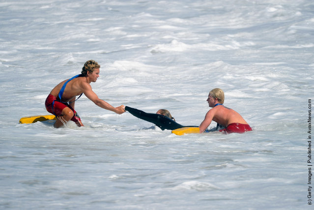 Lifegaurds help pull a woman out of the ocean as high waves measuring up to 20 feet pounded the beach at the Wedge
