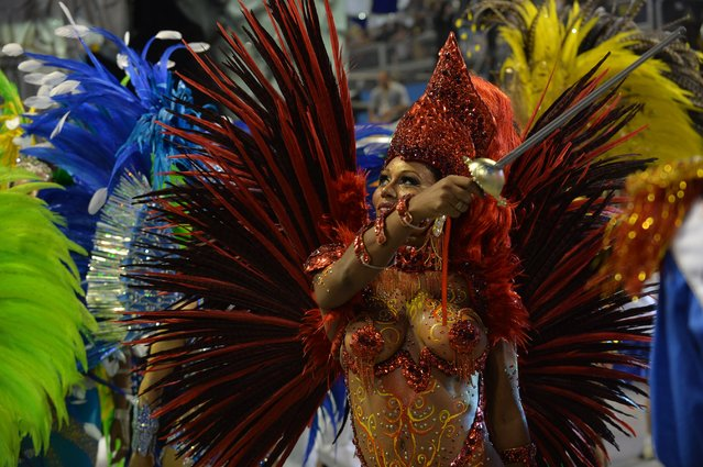 A reveler of the Academicos do Tatuape samba school performs during the second night of carnival parade at the Sambadrome in Sao Paulo, Brazil on March 2, 2014. (Photo by Nelson Almeida/AFP Photo)