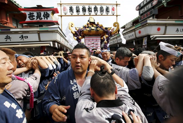 Revellers carry a portable shrine through a narrow row of market stalls outside the Sensoji temple during the Sanja Matsuri festival in the Asakusa district of Tokyo May 17, 2015. (Photo by Thomas Peter/Reuters)