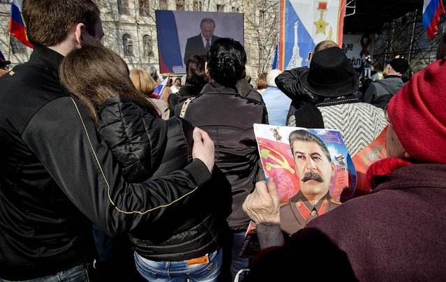 An elderly woman holds a calendar depicting former Soviet leader Josef Stalin while watching a broadcast of Russian President Vladimir Putin's speech on Crimea, seen in background, in Sevastopol, Crimea, Tuesday, March 18, 2014, as thousands of pro-Russian people gathered to watch the address.  Fiercely defending Russia's move to annex Crimea Putin said Russia had to respond to what he described as a western plot to take Ukraine into its influence. (Photo by Vadim Ghirda/AP Photo)
