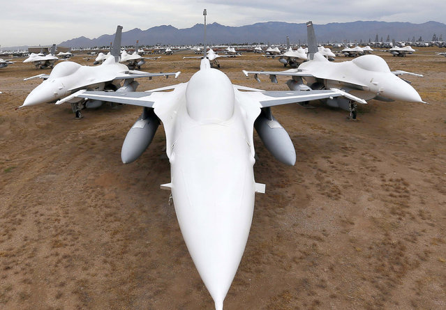 F-16 Fighting Falcons covered in sealing paint sit in a field along Miami St. at the 309th Aerospace Maintenance and Regeneration Group boneyard at Davis-Monthan Air Force Base in Tucson, Ariz. on Thursday, May 21, 2015. Over 4,500 variants of the F-16's have been produced since 1973. This field of fighters will become drone target planes in the future. (Photo by Matt York/AP Photo)