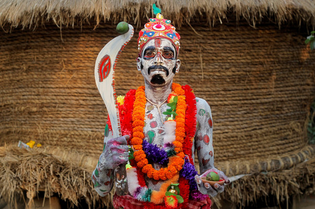 A devotee with his body painted poses as he waits to perform during a ritual as part of the annual Shiva Gajan religious festival at Sona Palasi village, in West Bengal, India, April 11, 2016. Devotees offer sacrifices and perform acts of devotion during the festival in the hopes of winning the favour of Hindu god Shiva and ensuring the fulfillment of their wishes, and also to mark the end of the Bengali calendar year. (Photo by Rupak De Chowdhuri/Reuters)