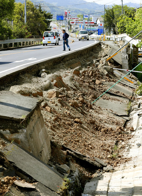 A man walks on a road damaged by a magnitude-6.5 earthquake in Mashiki, Kumamoto prefecture, southern Japan, Friday, April 15, 2016. (Photo by Yusuke Ogata/Kyodo News via AP Photo)