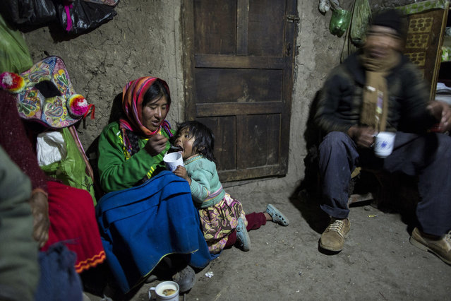 """In this February 4, 2017 photo, Maria Avila feeds her daughter Shomara in their family's adobe home in Coata, a village on the shored of Lake Titicaca in the Puno region of Peru. Avila grew angry as she talked about the lake's contamination. """"My ancestors have lived here more than 500 years. They have never gone through these things"""", she said. (Photo by Rodrigo Abd/AP Photo)"""