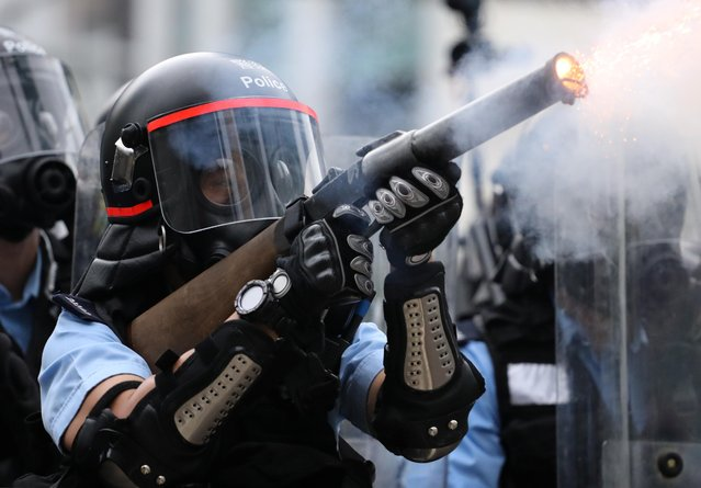 Police officer fires a tear gas during a demonstration against a proposed extradition bill in Hong Kong, China on June 12, 2019.. (Photo by Athit Perawongmetha/Reuters)