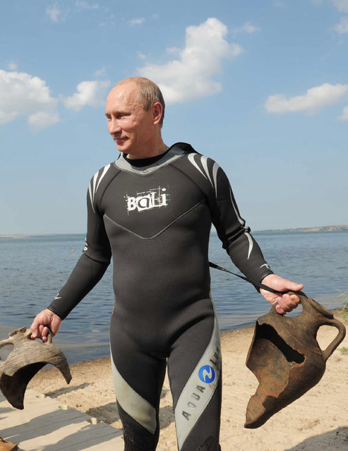 In this Wednesday, August 10, 2011 photo then Russian Prime Minister Vladimir Putin carries two pieces of archaeological trophies he discovered during diving near an archeological excavation of an ancient Greek port on the Taman Peninsula, about 1150 kilometers (720 miles) south of Moscow, Russia. (Photo by Alexei Druzhinin/AP Photo/RIA Novosti)