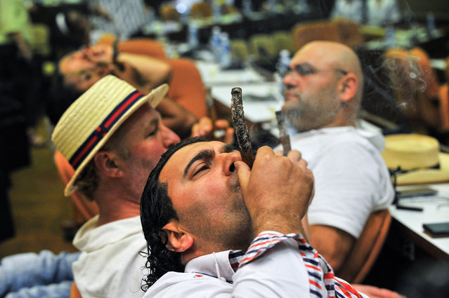 """Men smoke cigars during the contest for the longest ash during the XVII Havana Cigar Festival in Havana, on February 26, 2015. The world's largest Havana cigar festival comes as the industry possibly looks forward to a booming future following the historic announcement in December by US and Cuban leaders of moves to normalize relations after half a century. The 17th Habanos festival will honor Winston Churchill's beloved """"Romeo and Juliet"""" cigars at the opening of the five-day event to commemorate the 50th anniversary of the former British prime minister's death. (Photo by Yamil Lage/AFP Photo)"""