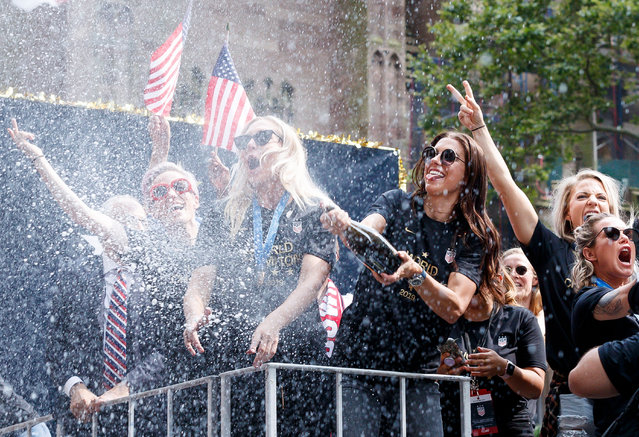 US Women's soccer player Alex Morgan (3-R) sprays champagne into the crowd during a ticker tape parade celebrating the team's 2019 World Cup victory along Broadway in New York, New York, USA, 10 July 2019. The US Women's national soccer team won the FIFA world cup in France for the fourth time in their history. (Photo by Justin Lane/EPA/EFE)