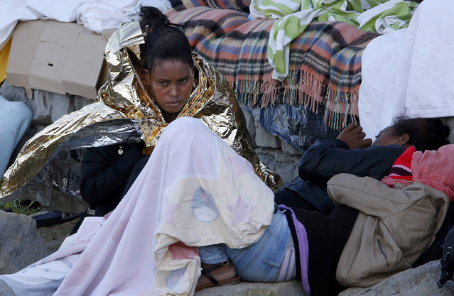 Migrants wrapped in blankets rest on the rocks of the seawall at the Saint Ludovic border crossing on the Mediterranean Sea between Vintimille, Italy and Menton, France, June 17, 2015. Police on Tuesday began hauling away mostly African migrants from makeshift camps on the Italy-France border as European Union ministers met in Luxembourg to hash out plans to deal with the immigration crisis.   REUTERS/Eric Gaillard