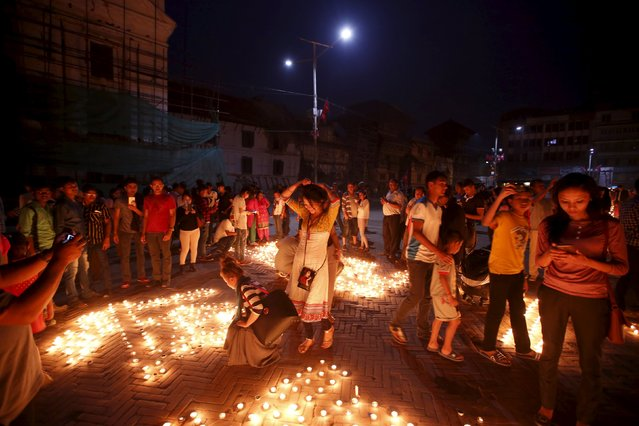 People gather along lit candles creating the shape of historic nine-storey Dharara tower and Kasthamandap temple to mark the first anniversary of the 2015 earthquakes at Bashantapur Durbar Square in Kathmandu, Nepal, April 24, 2016. (Photo by Navesh Chitrakar/Reuters)