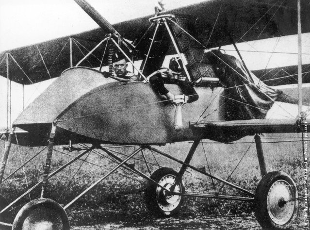 A Russian officer fastens a bomb to the side of his warplane before take off, 1915