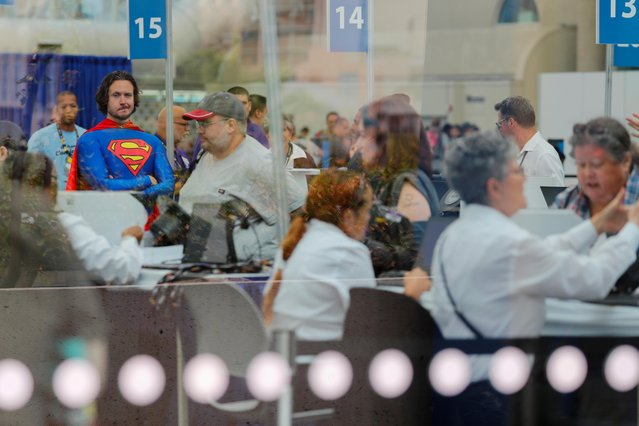 Volunteer Chris Perry dressed in a Superman costume, watches over attendees as they arrive at the pop culture festival Comic Con International in San Diego, California,U.S., July 17, 2019. (Photo by Mike Blake/Reuters)