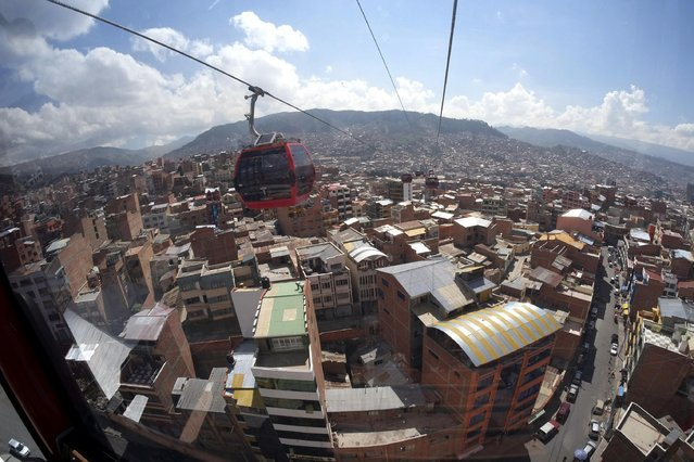 Cable cars are seen over La Paz April 8, 2014. Austria's Doppelmayr Garaventa Group held a media preview on Tuesday for the first of three urban ropeways in the Bolivian capital of La Paz. The first ropeway links the cities of La Paz and El Alto. The three ropeways will have an overall length of almost 11 km (6.835 miles) and a total of 11 stations, forming the world's largest network of urban ropeways and easing the traffic on congested roads, according to Doppelmayr. (Photo by David Mercado/Reuters)