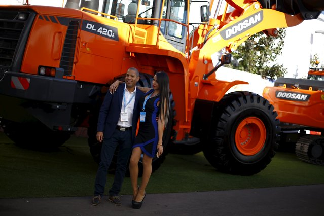 """A man poses with a promotional model at the """"Expomin"""" Chilean biennial mining fair in Santiago, Chile April 26, 2016. (Photo by Ivan Alvarado/Reuters)"""