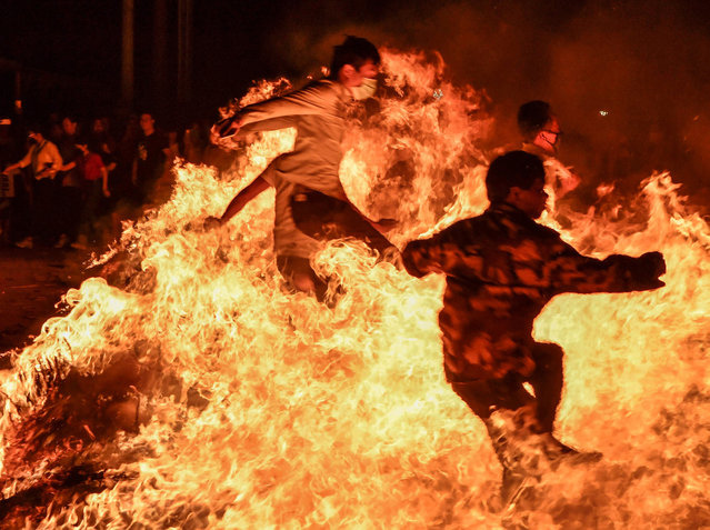 This photo taken on February 19, 2019 shows people jumping over a bonfire during an event to celebrate the Lantern Festival, which marks the end of Lunar New Year celebrations, in Haikou in China's southern Hainan province. (Photo by AFP Photo/Stringer)