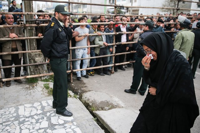Samereh Alinejad (R), the mother of Abdolah Hosseinzadeh who was killed by a fellow Iranian, Balal, in a street fight with a knife in 2007, cries after she spared the life of her son's convicted murderer with an emotional slap in the face as he awaited execution with the noose around his neck in the northern city of Nowshahr on April 15, 2014. (Photo by Araash Khamooshi/AFP Photo/ISNA)