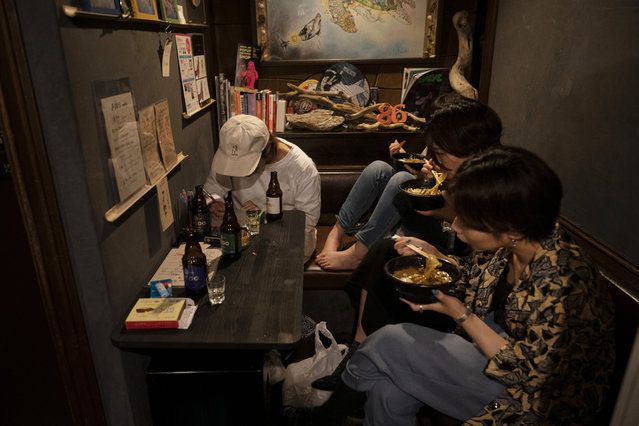 A group of Japanese women are crammed around a table as they eat their dinner in a bar at the Golden Gai in the Shinjuku district of Tokyo, July 17, 2019. (Photo by Jae C. Hong/AP Photo)