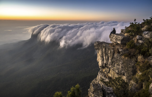 Clouds in Drakensberg Escarpment in the lowveld, also known as Mariepskop, South Africa in July 2019. Snapped by professional Photographer, Em Gatland, 37, from Greater Kruger, South Africa, the unique shot could easily be mistaken for a dangerous wave rather than clouds passing through a sunset. (Photo by Em Gatland/Caters News Agency)