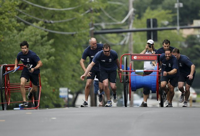 The team from the South Australian Country Fire Service in Melbourne sprint from the start line in the hose cart competition during the Firefighter Muster event at the World Fire and Police Games in Fairfax, Virginia July 4, 2015. (Photo by Jonathan Ernst/Reuters)