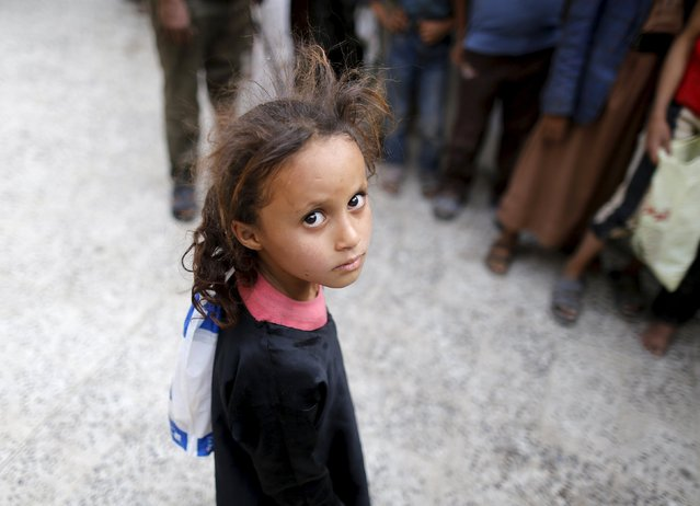 A girl waits for her family's ration at a food assistance center run by volunteers in Yemen's capital Sanaa July 1, 2015. (Photo by Khaled Abdullah/Reuters)