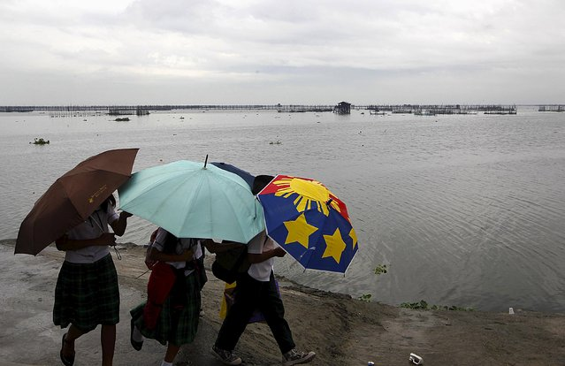 School girls with umbrellas take a stroll after classes were suspended due to bad weather, at a park in front of Laguna de Bay, in Paranaque, Metro Manila July 6, 2015. (Photo by Marconi Navales/Reuters)