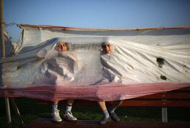 Palestinian children play under a tarp at the harbour in Gaza City on April 28, 2014. (Photo by Mohammed Abed/AFP Photo)
