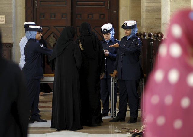 Police officers search women arriving at the entrance of Bahrain Sunni Grand Mosque, where joint Sunni and Shi'ites Friday prayers were held to show solidarity and co-existence between the two sects of Islam, in Juffair east  of Manama, Bahrain, July 10, 2015. (Photo by Hamad I. Mohammed/Reuters)