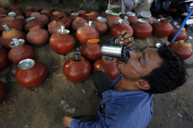 An Indian man drinks water from an earthen pot kept by the side of a road for people on a hot day in Ahmadabad, India, Friday, April 21, 2017. Most of north India has been reeling under a heat wave with temperatures rising above 40 degrees Celsius. (Photo by Ajit Solanki/AP Photo)