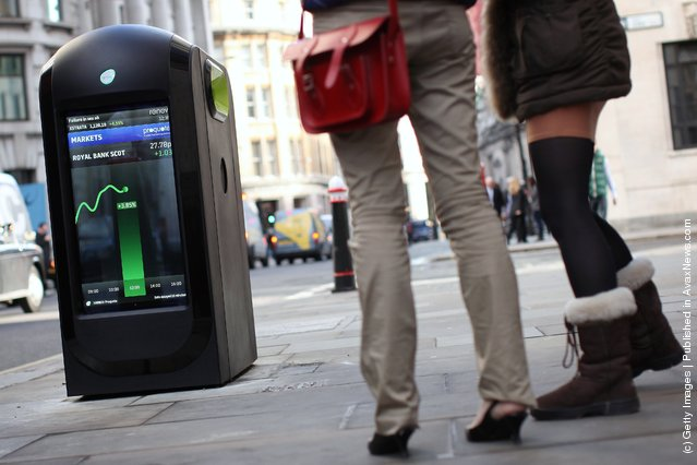 People look at a newly installed 'Renew' media point in the City of London