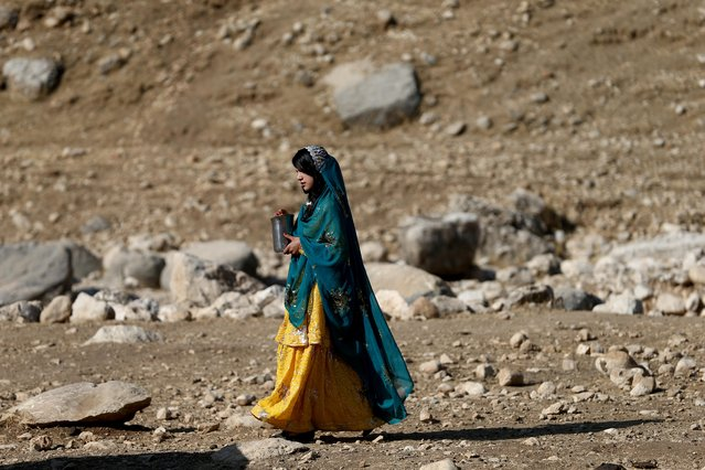 An Iranian woman walks during the traditional wedding of Sahar and Zal Sahbazi, Iranian nomad bride and groom, at Bazoft town in Chaharmahal and Bakhtiari Province, Iran August 27, 2019. (Photo by Nazanin Tabatabaee/WANA (West Asia News Agency) via Reuters)