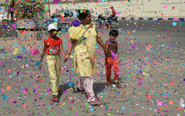 An Indian resident walks through coloured streamer paper thrown during a procession by the Chief Minister of the western state of Gujarat and main opposition Bharatiya Janata Party (BJP) prime ministerial candidate Narendra Modi in Ahmedabad on May 15, 2014. (Photo by Indranil Mukherjee/AFP Photo)