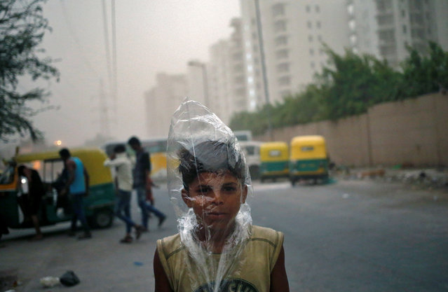 A young boy uses a plastic bag to protect himself from a dust storm in New Delhi, India May 23, 2016. (Photo by Anindito Mukherjee/Reuters)