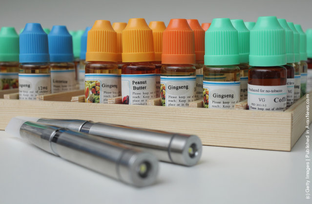 Two electronic cigarettes lie in front of bottles containing the flavoured liquids they use at a shop