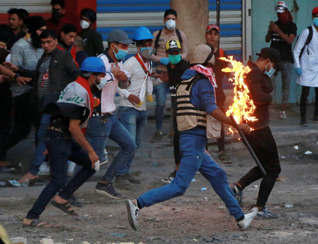 Demonstrators try to extinguish a protester who has caught fire, during clashes between Iraqi security forces and anti-Government protesters, in Baghdad, Iraq, Thursday, November 21, 2019. Iraqi officials said several protesters were killed as heavy clashes erupt in central Baghdad. (Photo by Khalid Mohammed/AP Photo)